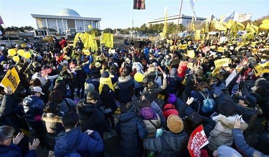 韓国の国会議事堂(奥左)近くで、朴槿恵大統領の弾劾訴追案可決を喜ぶ人たち=9日(共同)