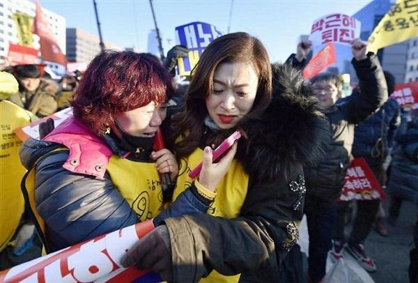 韓国の国会近くで、朴槿恵大統領の弾劾訴追案可決を知り涙を流して喜ぶ人たち=9日(共同)