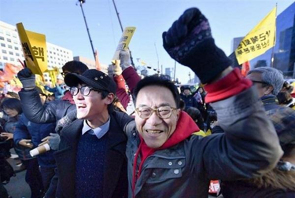 韓国の国会近くで、朴槿恵大統領の弾劾訴追案可決を知り喜ぶ人たち=9日(共同)