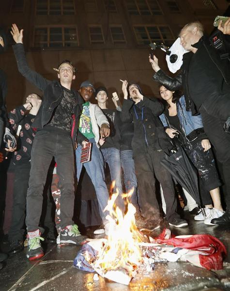 ニューヨークのトランプタワー前で、米大統領選で勝利を決めたトランプ氏に抗議し、星条旗に火を付けるデモ隊