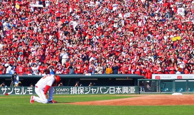 優勝報告会でマウンドの前でひざまずく広島の黒田博樹投手