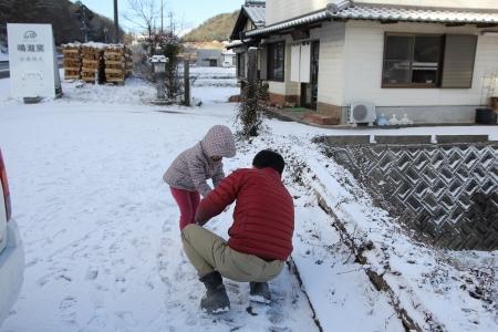雪だるまを制作する父と子